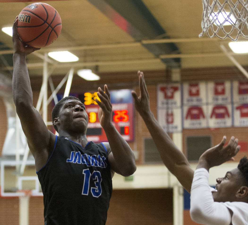Desert Pines junior Darnell Washington (13) drives to the rim over Bishop Gorman sophomore guard Zaon Collins (10) in the fourth quarter during the Southern Nevada boys basketball championship gam ...