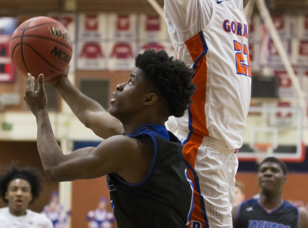 Desert Pines sophomore Semaj Threats (1) goes baseline past Bishop Gorman junior forward Mwani Wilkinson (23) in the fourth quarter during the Southern Nevada boys basketball championship game on ...
