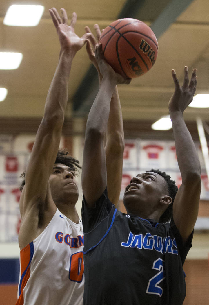 Desert Pines sophomore Dayshawn Wiley (2) grabs a rebound over Bishop Gorman junior forward Isaiah Cottrell (0) in the fourth quarter during the Southern Nevada boys basketball championship game o ...