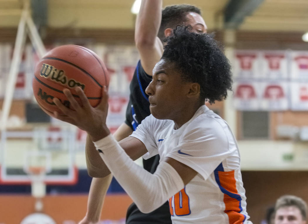 Bishop Gorman sophomore guard Zaon Collins (10) drives baseline past Desert Pines sophomore Cimarron Conriquez (3) in the third quarter during the Southern Nevada boys basketball championship game ...