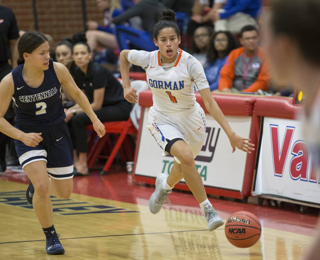 Bishop Gorman senior Caira Young (1) pushes the ball up court past Centennial senior Melanie Isbell (2) in the second quarter during the Southern Nevada girls basketball championship game on Monda ...