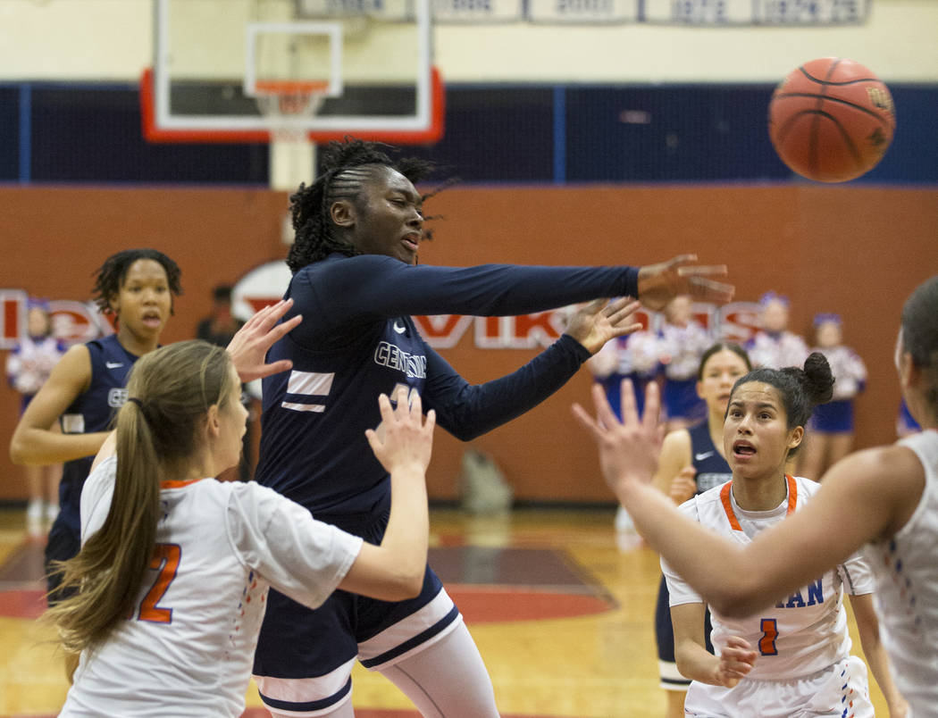 Centennial senior Eboni Walker (22) kicks the ball out to the corner past Bishop Gorman senior Caira Young (1) and senior Lexi Kruljac (22) in the third quarter during the Southern Nevada girls ba ...