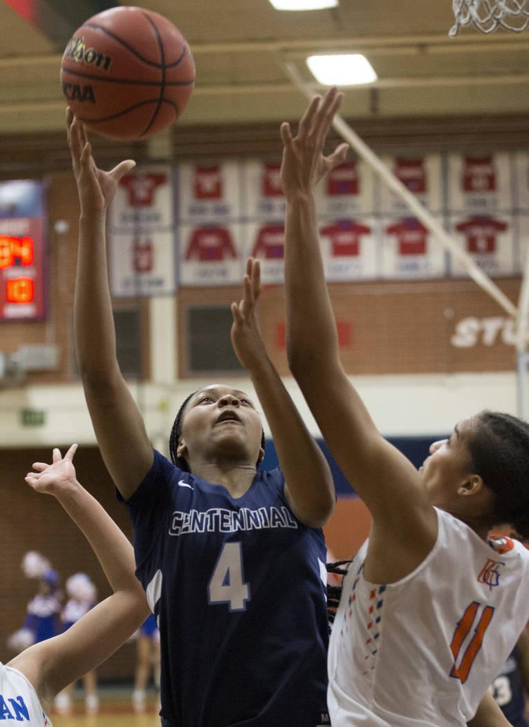 Centennial sophomore Taylor Bigby (4) drives past Bishop Gorman senior Olivia Smith (11) and senior Georgia Ohiaeri (13) in the fourth quarter during the Southern Nevada girls basketball champions ...