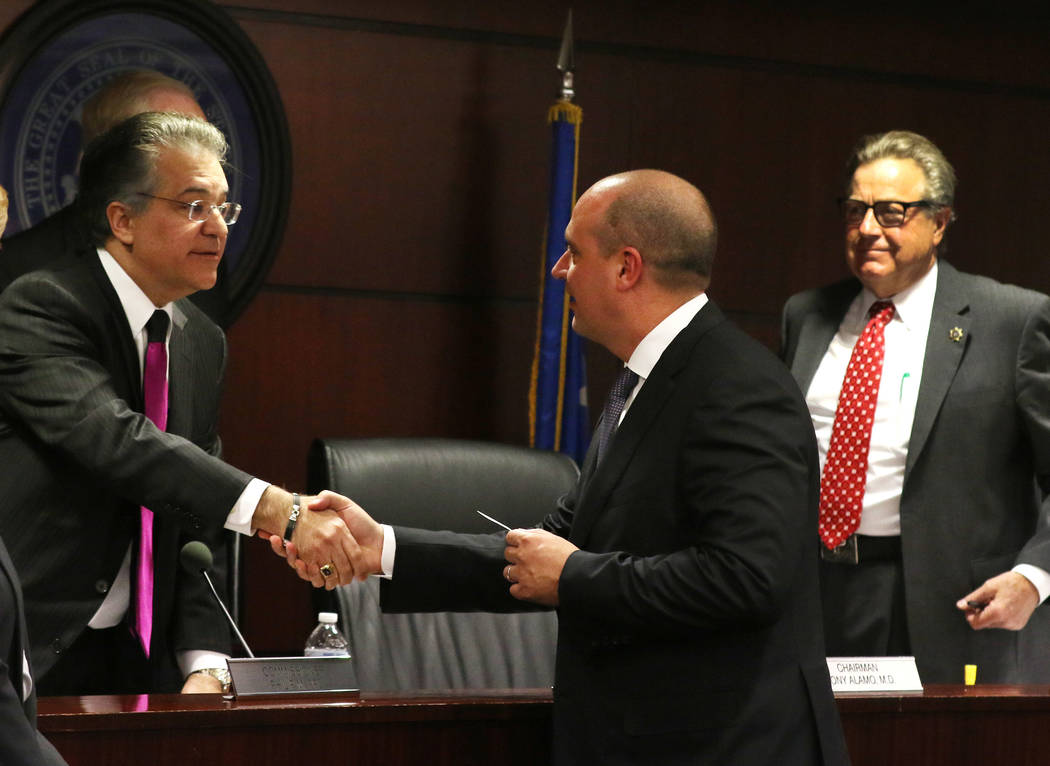 Dr. Tony Alamo, left, chairman of the Nevada Gaming Commission, shakes hands with Matt Maddox, CEO of Wynn Resorts Ltd., as Commissioner John T. Moran Jr., right looks on after a meeting of the Ne ...
