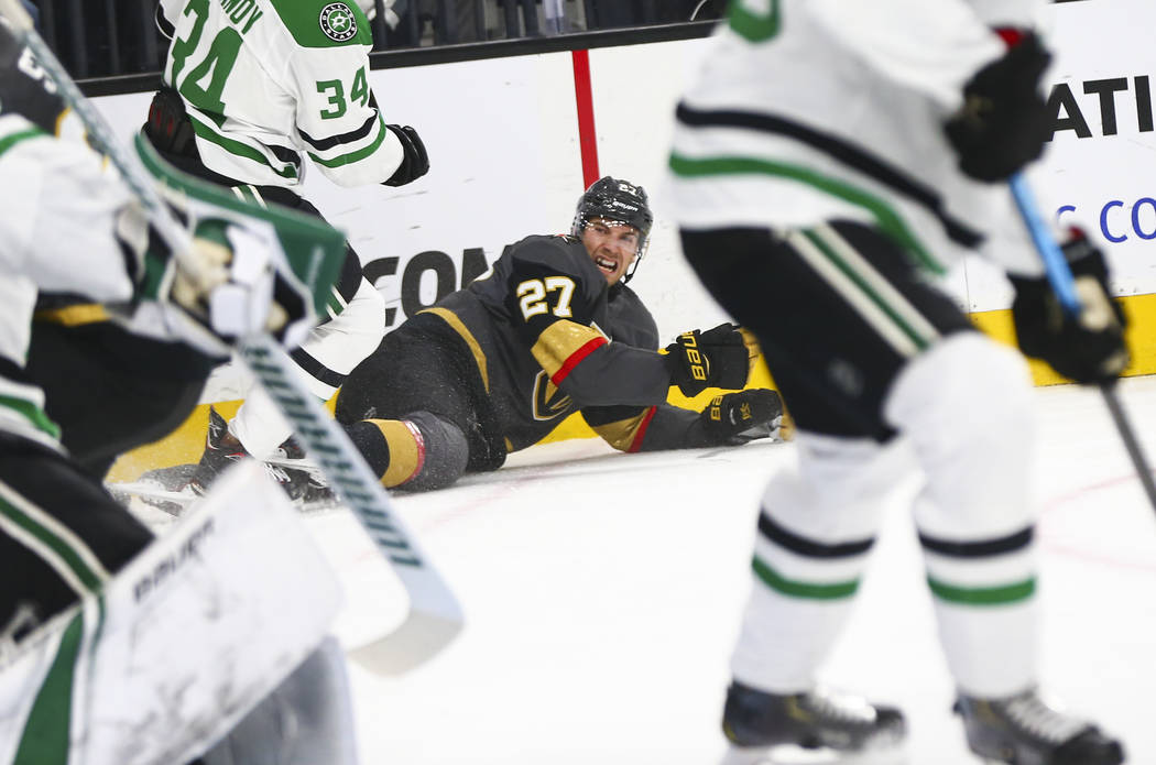 Golden Knights defenseman Shea Theodore (27) gets tripped up during the first period of an NHL hockey game against the Dallas Stars at T-Mobile Arena in Las Vegas on Tuesday, Feb. 26, 2019. (Chase ...
