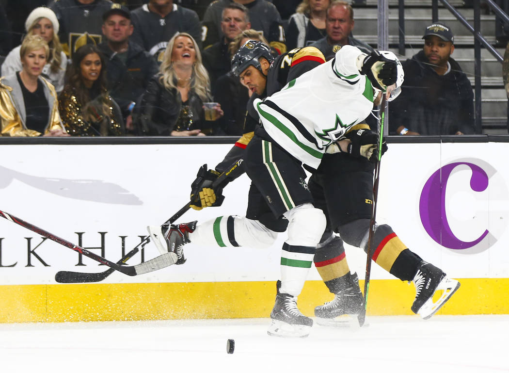 Golden Knights right wing Ryan Reaves, left, and Dallas Stars center Jason Dickinson get tripped up during the first period of an NHL hockey game at T-Mobile Arena in Las Vegas on Tuesday, Feb. 26 ...