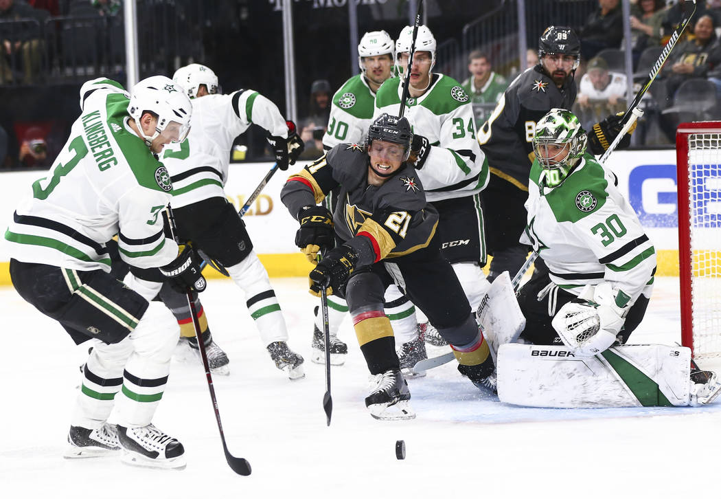 Golden Knights center Cody Eakin (21) chases after a loose puck against Dallas Stars defenseman John Klingberg (3) while goaltender Ben Bishop (30) looks on during the second period of an NHL hock ...