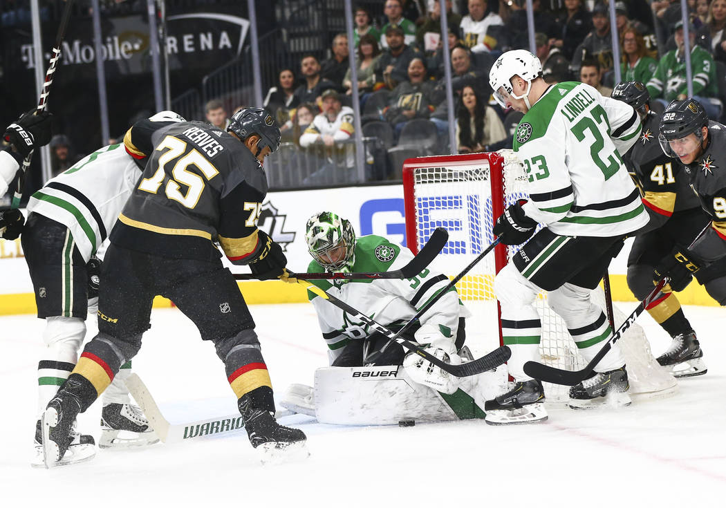 Golden Knights right wing Ryan Reaves (75) tries to get the puck in against Dallas Stars goaltender Ben Bishop (30) and defenseman Esa Lindell (23) during the second period of an NHL hockey game a ...