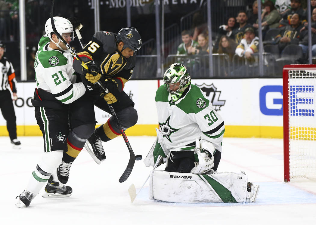 Golden Knights right wing Ryan Reaves (75) tries to get the puck in under pressure from Dallas Stars defenseman Ben Lovejoy (21) while Dallas Stars goaltender Ben Bishop (30) defends during the se ...