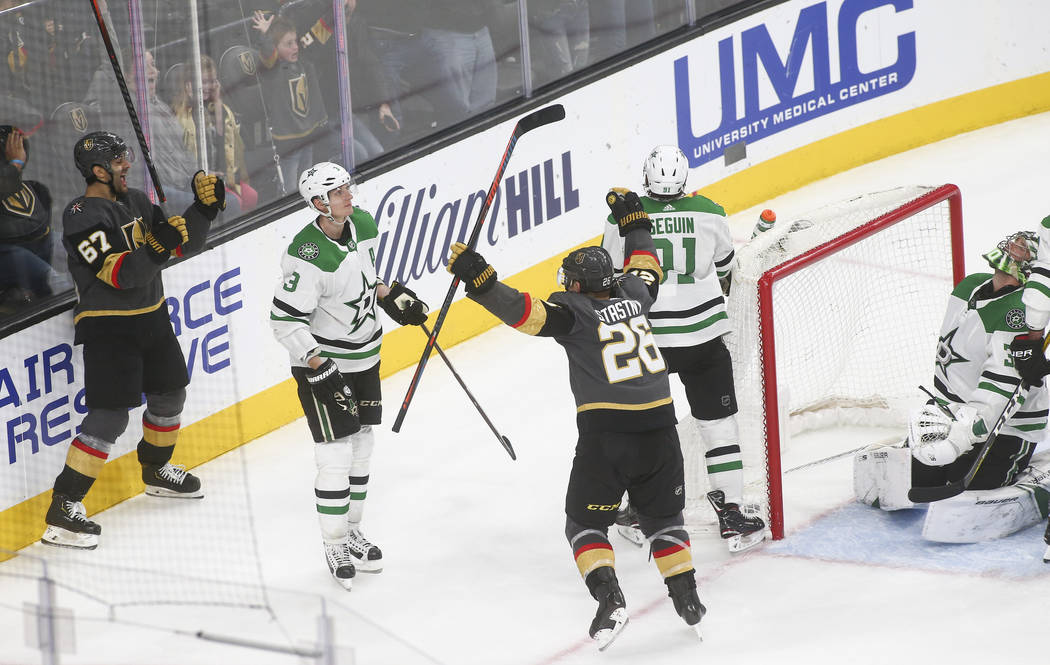 Golden Knights left wing Max Pacioretty (67) celebrates his goal with Golden Knights center Paul Stastny (26) as Dallas Stars goaltender Ben Bishop, far right, reacts during the third period of an ...