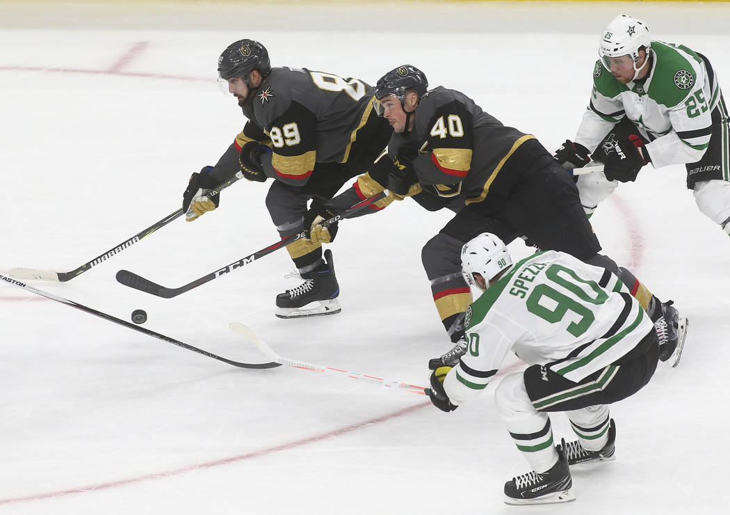 Golden Knights center Ryan Carpenter (40) skates with the puck alongside right wing Alex Tuch (89) while under pressure from Dallas Stars center Jason Spezza (90) and right wing Brett Ritchie (25) ...