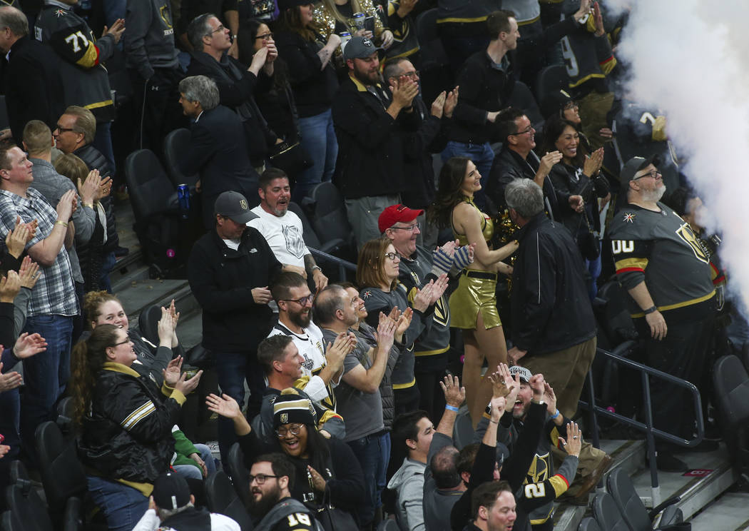 Golden Knights fans celebrate an empty net goal by Golden Knights defenseman Nate Schmidt, not pictured, during the third period of an NHL hockey game against the Dallas Stars at T-Mobile Arena in ...