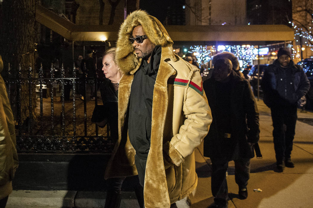 R. Kelly walks to his vehicle after exiting a cigar lounge in Chicago on Monday, Feb. 25, 2019. A suburban Chicago woman posted the $100,000 bail for R. Kelly to be freed from jail while he await ...