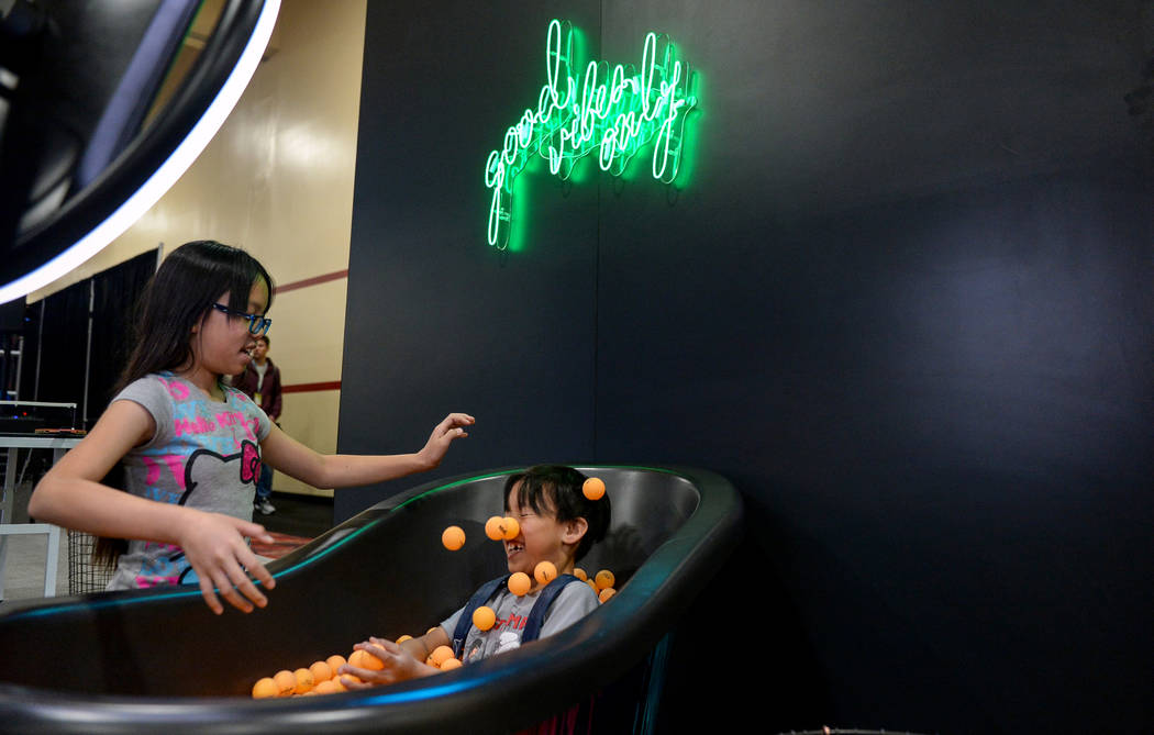 Delilah Crisostomo, 10, throws ping pong balls on her brother, Davis Crisostomo, 8, at the Simple Booth stand at the Photo Booth Expo at the South Point Hotel and Casino in Las Vegas, Tuesday, Feb ...