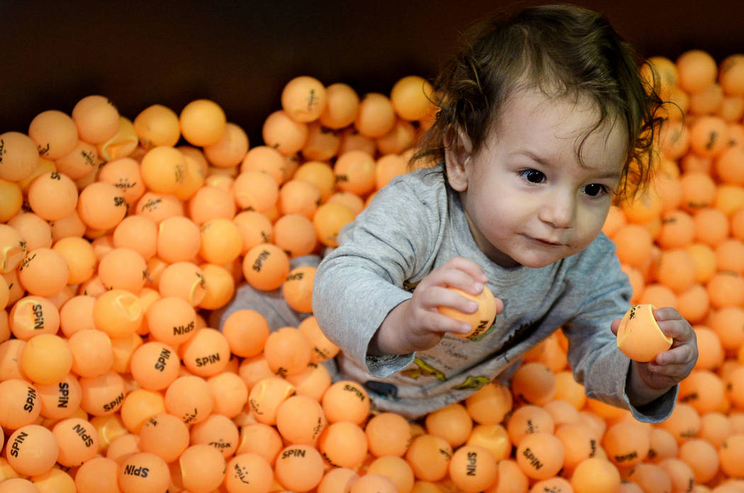 Atlas Varela, 13 months, sits in a bathtub full of ping pong balls at the Simple Booth stand at the Photo Booth Expo at the South Point Hotel and Casino in Las Vegas, Tuesday, Feb. 26, 2019. (Caro ...
