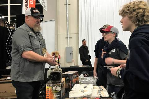 A group of young hunters listens intently while Al Morris, host of FOXPRO Hunting TV, shares the finer points of using an electronic game call to hail coyotes during the Western Hunting & Conserva ...