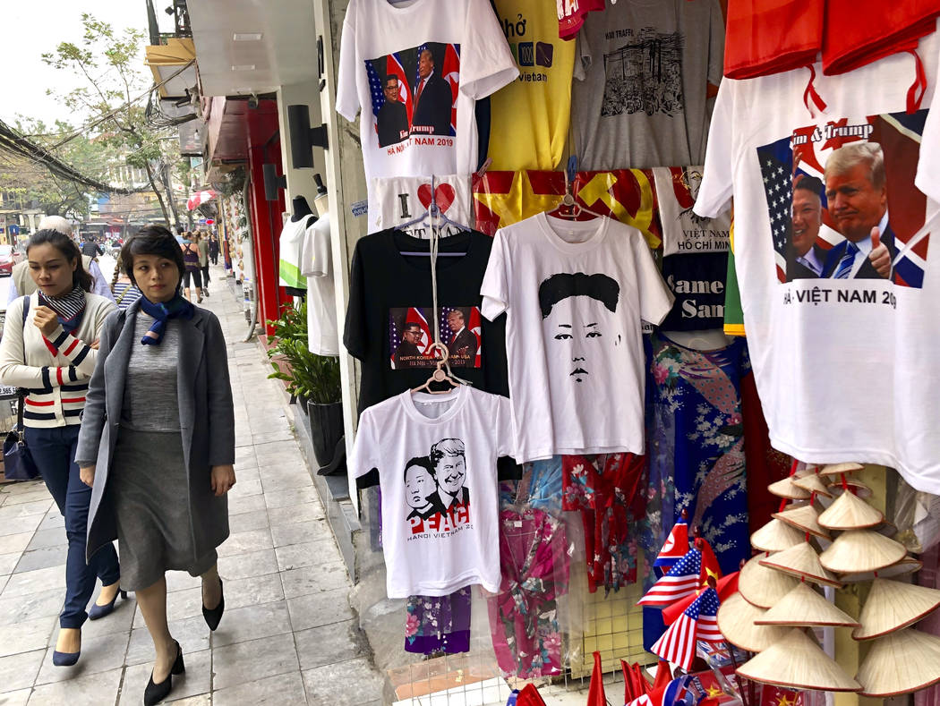 A woman glances at a shop selling t-shirts marking the summit between U.S. President Donald Trump and North Korean leader Kim Jong Un in Hanoi, Vietnam, Wednesday, Feb. 27, 2019. Trump hoped for & ...