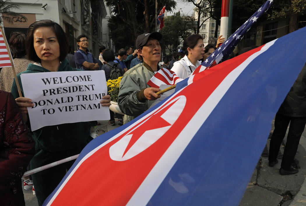 People hold placards and U.S. and North Korea flags outside the Metropole hotel where President Donald Trump and North Korean leader Kim Jong Un will have dinner in Hanoi, Vietnam, Wednesday, Feb. ...
