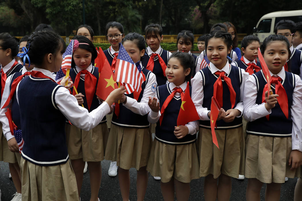 Children are handed American flags before U.S. President Donald Trump arrives to meet with Vietnamese President Nguyen Phu Trong at the Presidential Palace, Wednesday, Feb. 27, 2019, in Hanoi. (AP ...