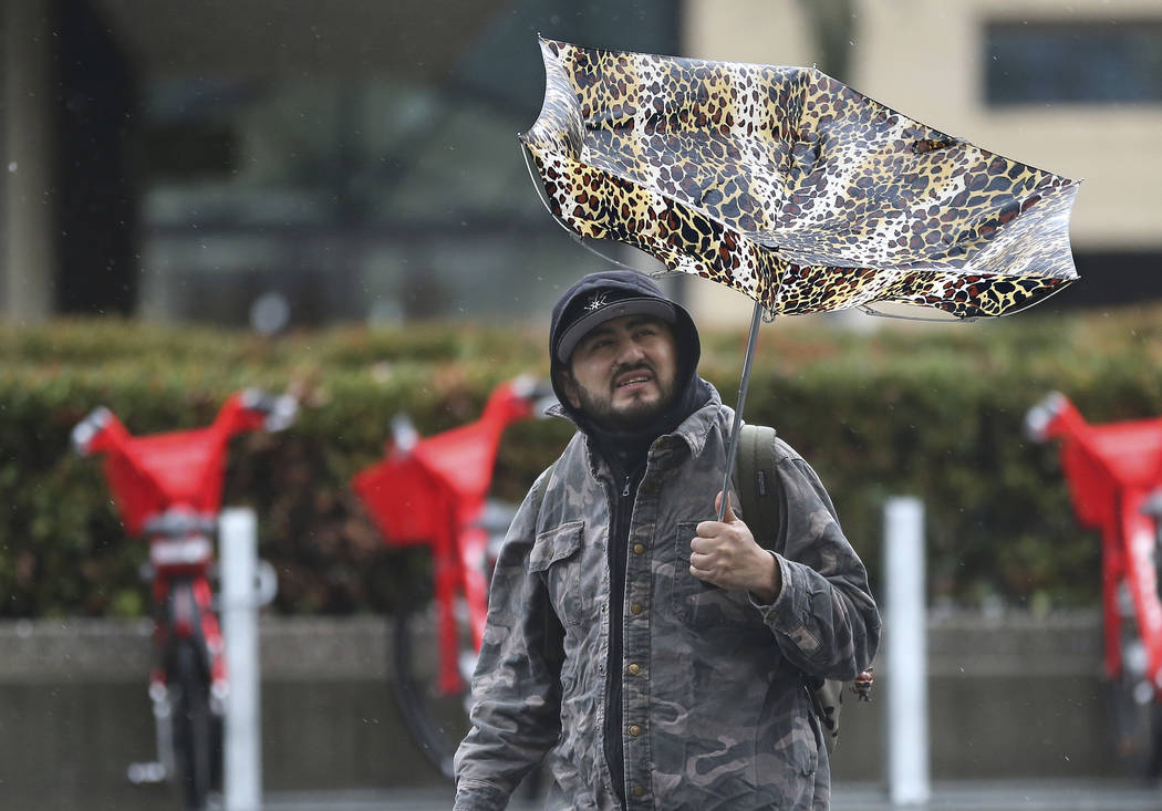 High winds caused havoc for a man using an umbrella as rain pelted Sacramento, Calif., Tuesday, Feb. 26, 2019. (AP Photo/Rich Pedroncelli)