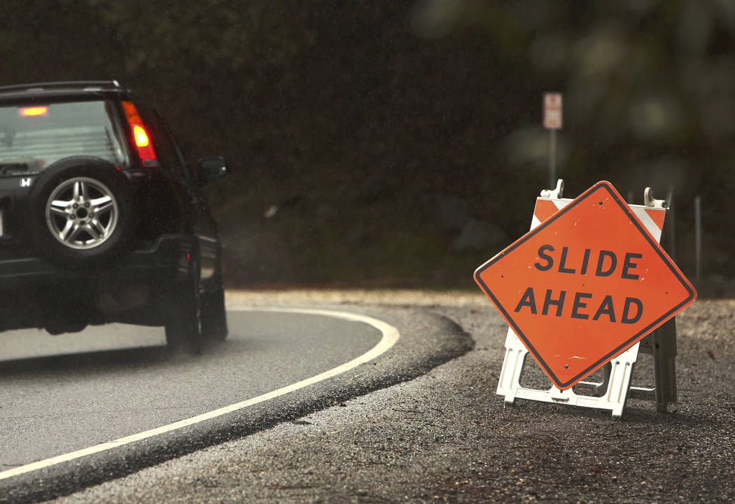 A vehicle makes its way down Highway 49 in the South Yuba River Canyon in Nevada City, Calif., Tuesday evening, Feb. 26, 2019. Torrential rain from a winter storm that has also dumped heavy snow i ...