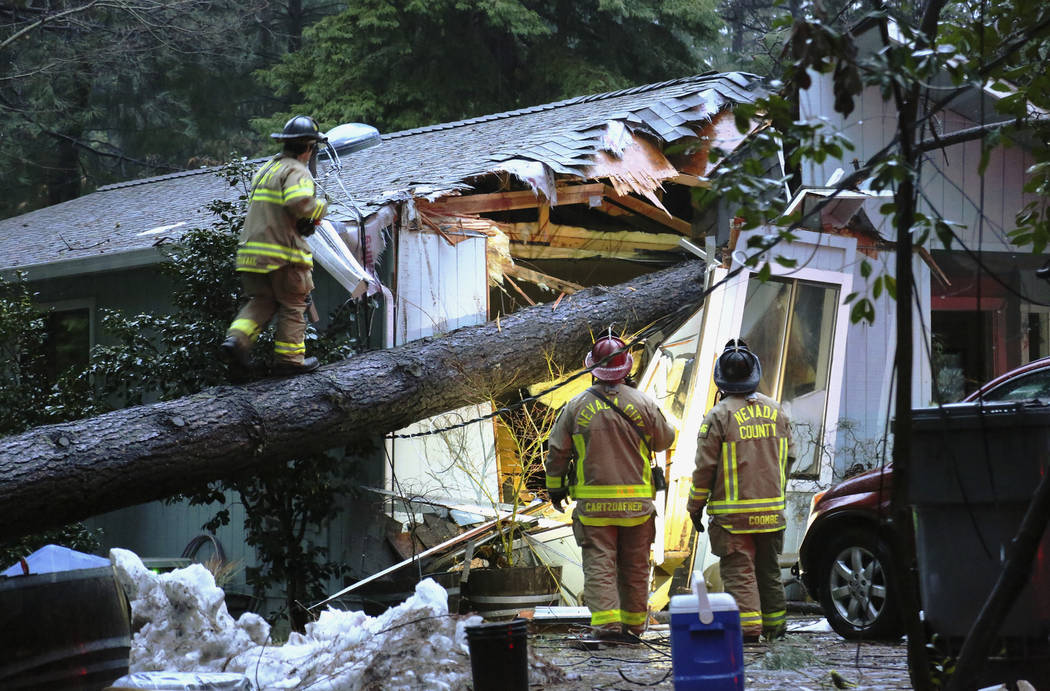 Nevada County and Nevada City firefighters work to assess a structure on Juniper Drive that sustained a tree fall, knocking out power and potentially causing a gas hazard in the process, Tuesday e ...