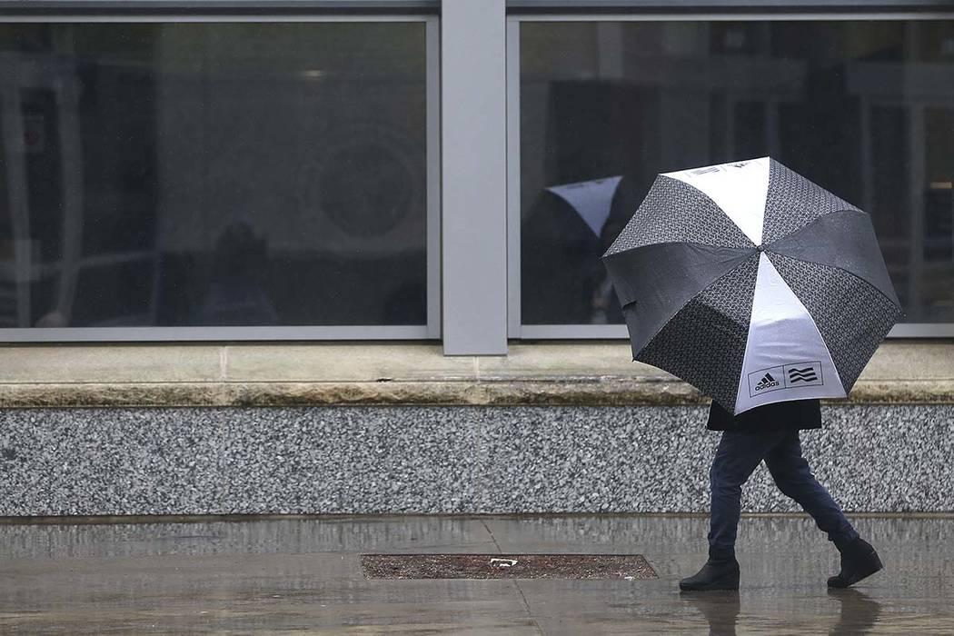 A pedestrain huddles under an umbrella as rain falls in Sacramento, Calif., Tuesday, Feb. 26, 2019. (AP Photo/Rich Pedroncelli)