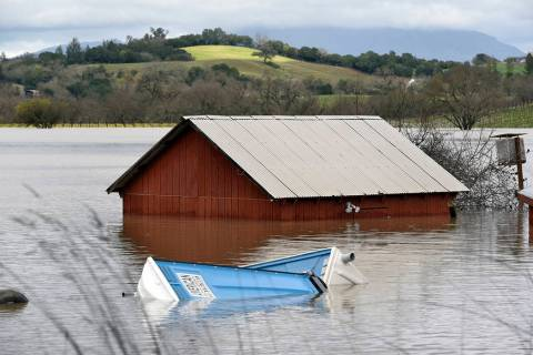 A barn and farm equipment are seen submerged in flood waters from the Russian River in Forestville, north of San Francisco, Wednesday, Feb. 27, 2019. (AP Photo/Michael Short)