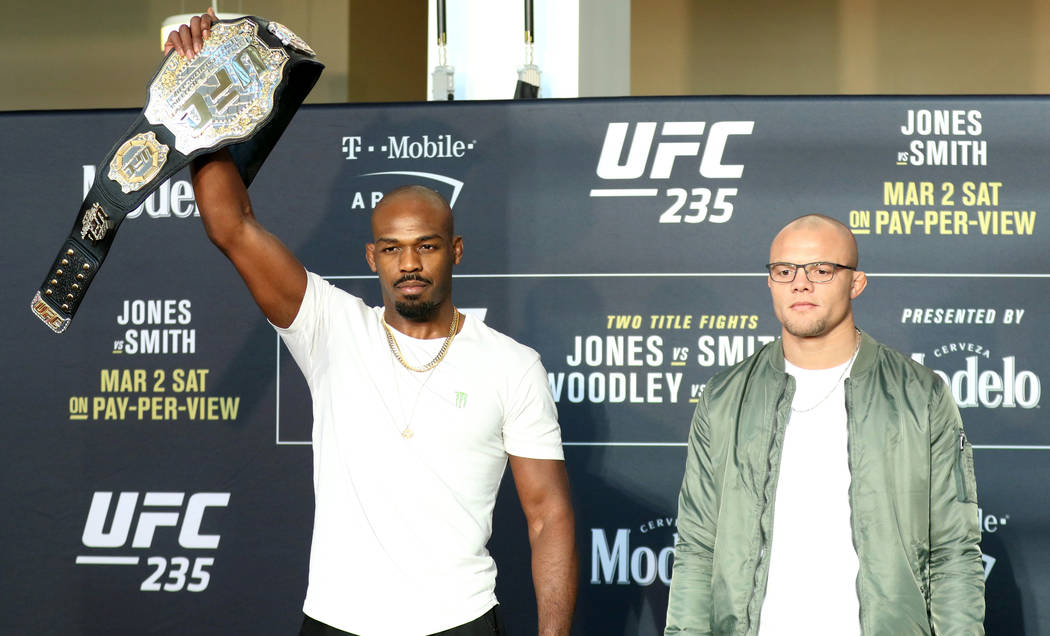 UFC light heavyweight champion Jon Jones raises his belt in the air as he stands next to his opponent, Anthony Smith at UFC 235 media day at the T-Mobile Arena in Las Vegas, Wednesday, Feb. 27, 20 ...