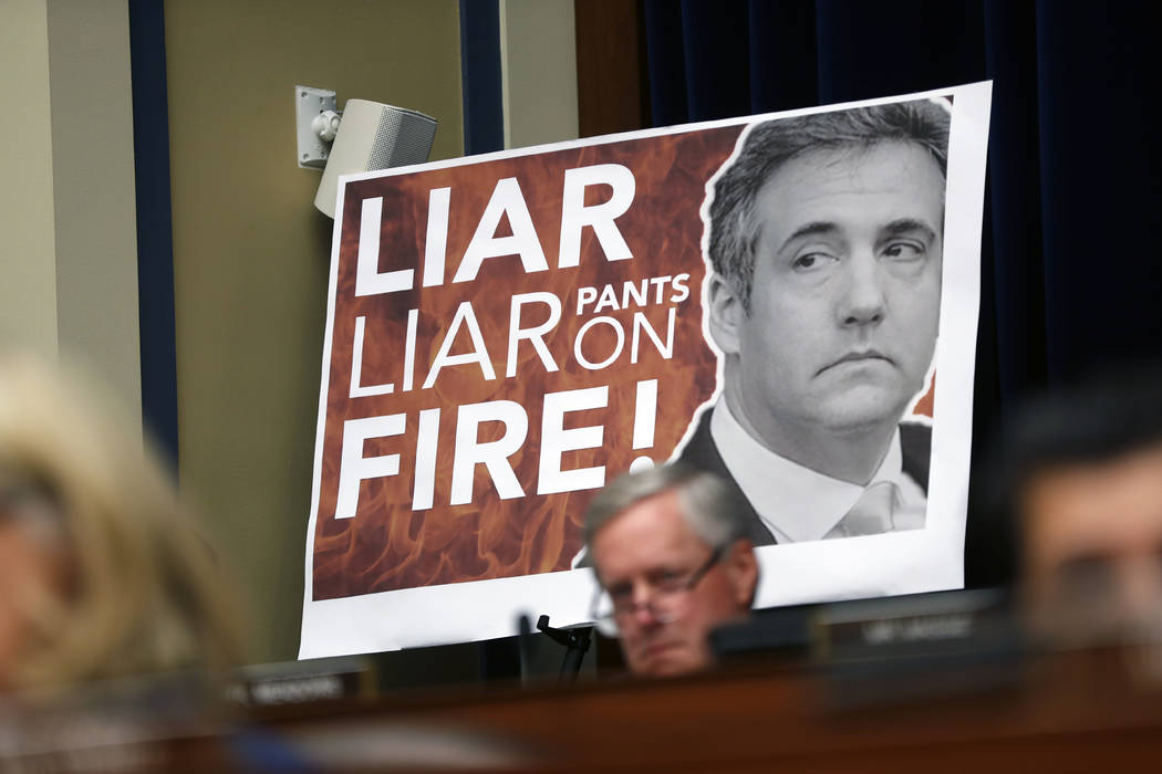 A poster on display during a hearing with Michael Cohen, President Donald Trump's former personal lawyer, before the House Oversight and Reform Committee on Capitol Hill in Washington, Wednesday, ...