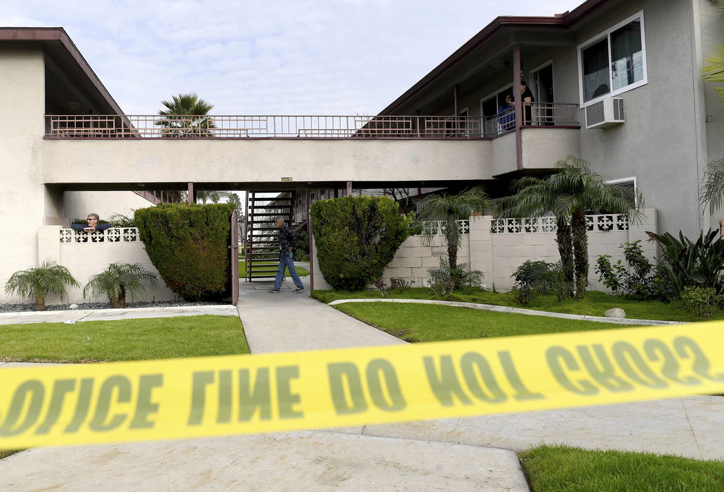 Residents mill about as Upland police investigate the scene, where police say a mother threw her young son from the second-story balcony of an apartment complex and then jumped herself as police a ...