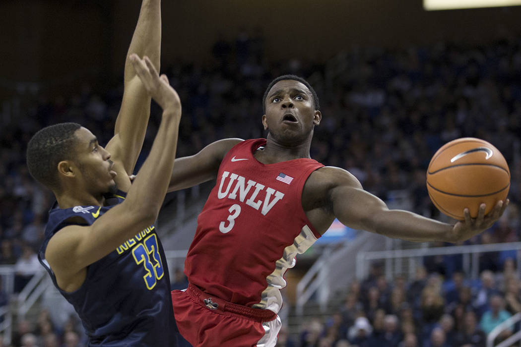UNLV's Amauri Hardy shoots around UNR's Josh Hall during the second half of an NCAA college basketball game in Reno, Nev., Wednesday, Feb. 7, 2018. (AP Photo/Tom R. Smedes)