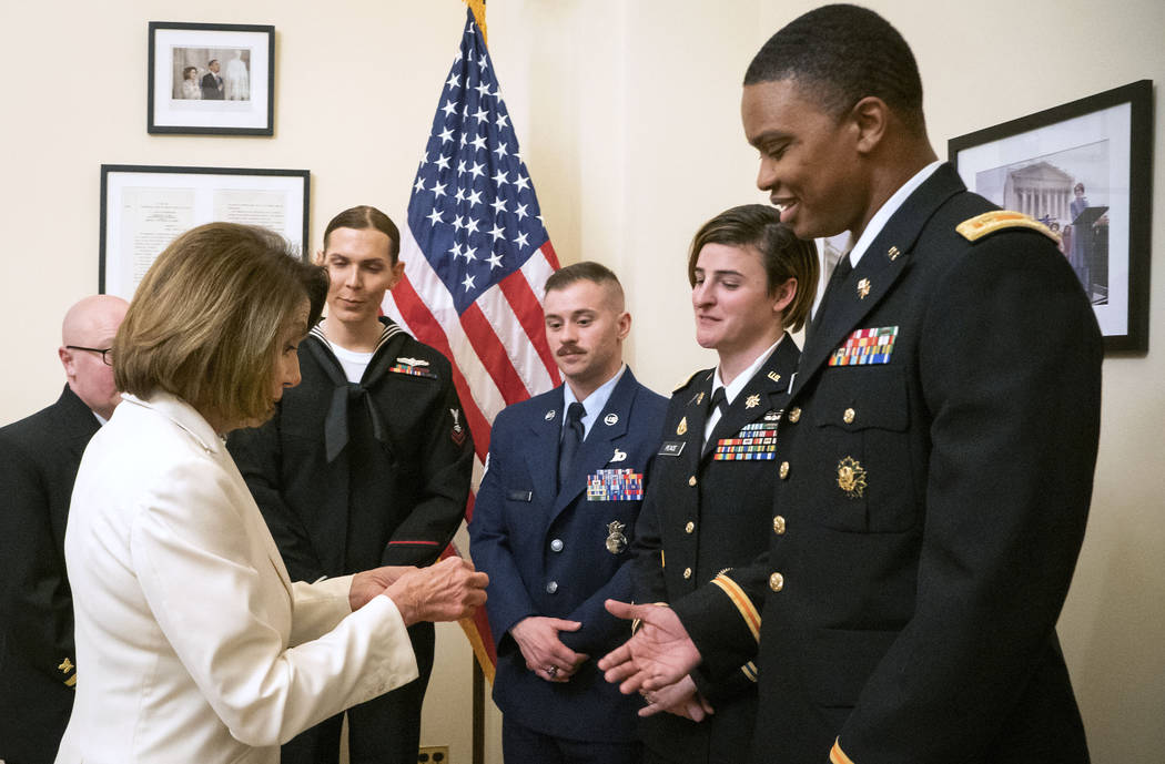 In this Tuesday, Feb. 5, 2019 photo released by the her office, Speaker of the House Nancy Pelosi, D-Calif., left, gives challenge coins to U.S. Army Maj. Ian Brown, right, and other military serv ...