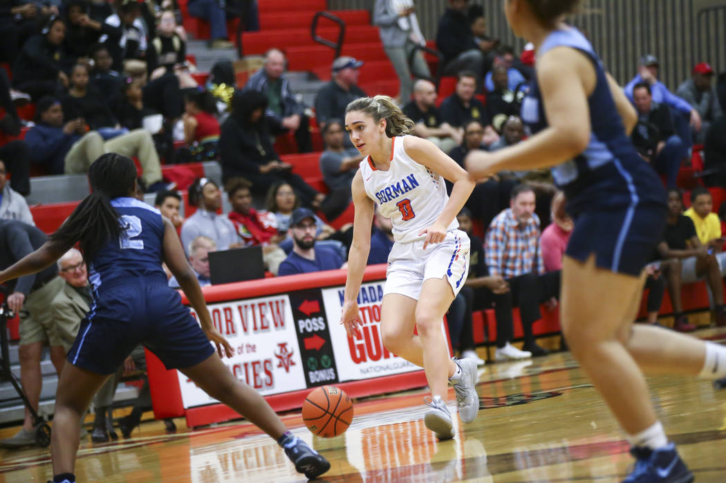 Bishop Gorman's Izzy Westbrook (0) brings the ball up court against Canyon Springs' Rajah Thomas (2) during the first half of a Class 4A state girls basketball quarterfinal game at Arbor View High ...