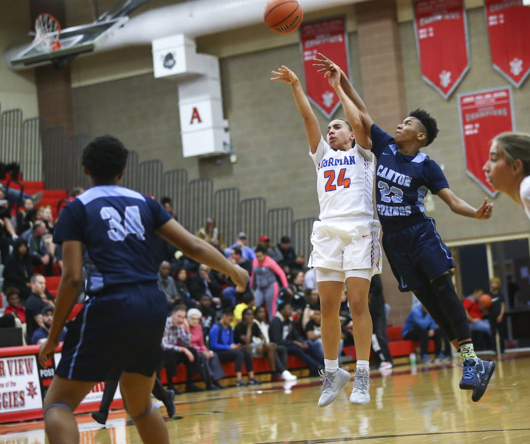 Bishop Gorman's Bentleigh Hoskins (24) shoots under pressure from Canyon Springs' Kayla Johnson (23) during the first half of a Class 4A state girls basketball quarterfinal game at Arbor View High ...