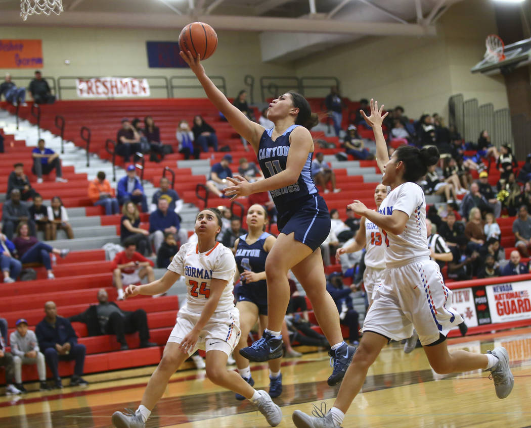 Canyon Springs' Jeanette Fine (11) goes to the basket over Bishop Gorman's Bentleigh Hoskins (24) during the second half of a Class 4A state girls basketball quarterfinal game at Arbor View High S ...