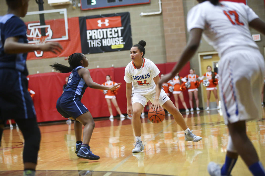 Bishop Gorman's Bentleigh Hoskins (24) moves the ball around Canyon Springs' Rajah Thomas (2) during the first half of a Class 4A state girls basketball quarterfinal game at Arbor View High School ...