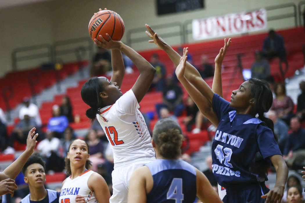 Bishop Gorman's Aaliyah Bey (12) shoots over Canyon Springs' Brooklyn Knox (42) during the first half of a Class 4A state girls basketball quarterfinal game at Arbor View High School in Las Vegas ...