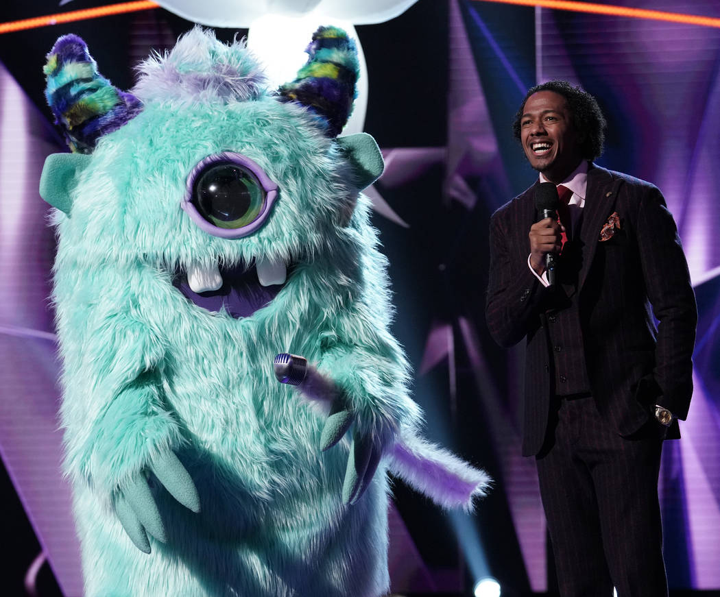 "The Monster and host Nick Cannon are seen in ""The Masked Singer."" (Michael Becker/Fox)"