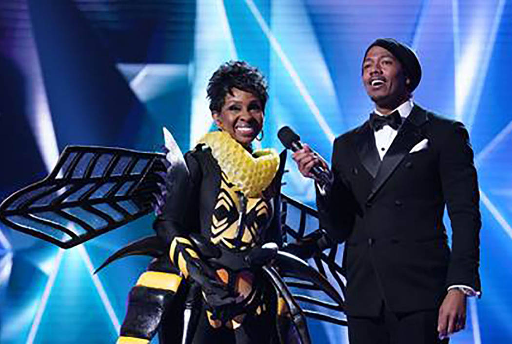 "The Bee is revealed as Gladys Knight during ""The Masked Singer."" With Knight is host Nick Cannon. (Fox)"