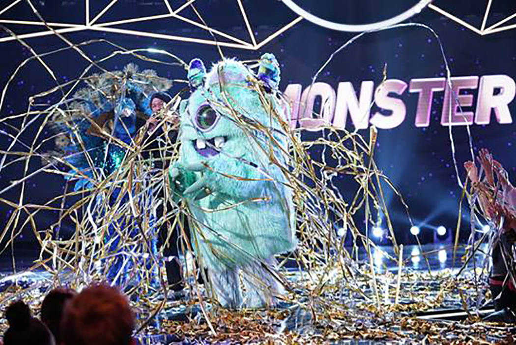 """The Monster and host Nick Cannon are seen in """"The Masked Singer."""" (Fox)"""
