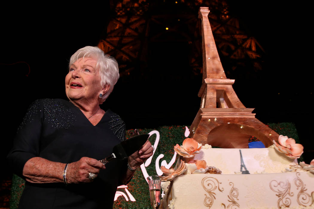 French singer and actress Line Renaud gets ready to cut an Eiffel Tower shaped cake as the Paris Las Vegas debuts a new $1.7 million Eiffel Tower light show on the Strip in Las Vegas, Wednesday, F ...