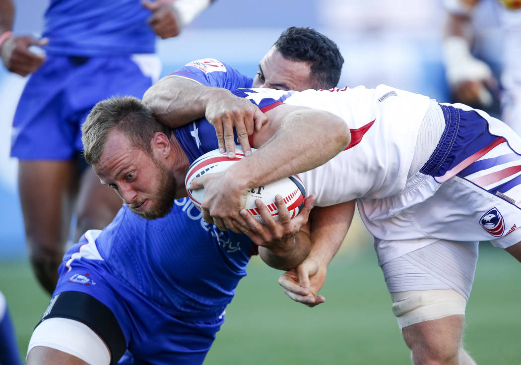 Ben Pinkelman of the US drives the ball for a try, worth five points, against Jacob Ale of Samoa during day one of the USA Sevens Rugby tournament at Sam Boyd Stadium ...
