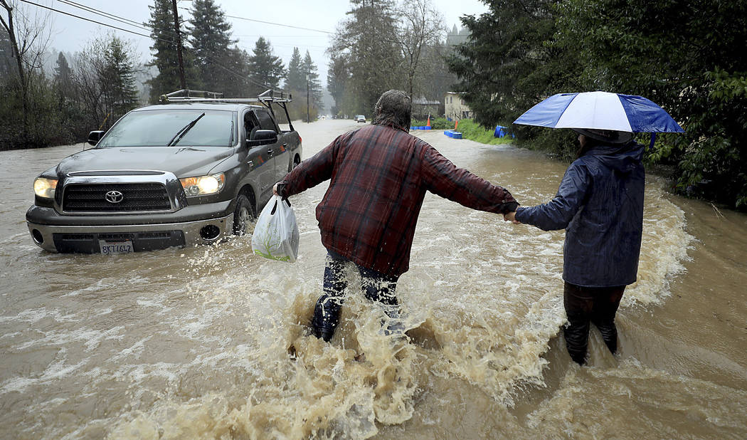 Residents along Armstrong Woods Road head back to their home after the road became impassable to most vehicles, Tuesday, Feb. 26, 2019 in Guerneville, Calif. (Kent Porter/The Press Democrat via AP)