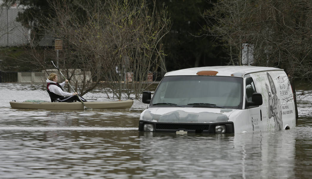 A man paddles past a submerged van in the flooded Barlow Market District parking lot Wednesday, Feb. 27, 2019, in Sebastopol, Calif. (Eric Risberg/AP)
