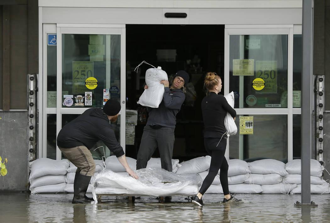 People unload sandbags in floodwater outside a market Wednesday, Feb. 27, 2019, in Sebastopol, Calif. (Eric Risberg/AP)