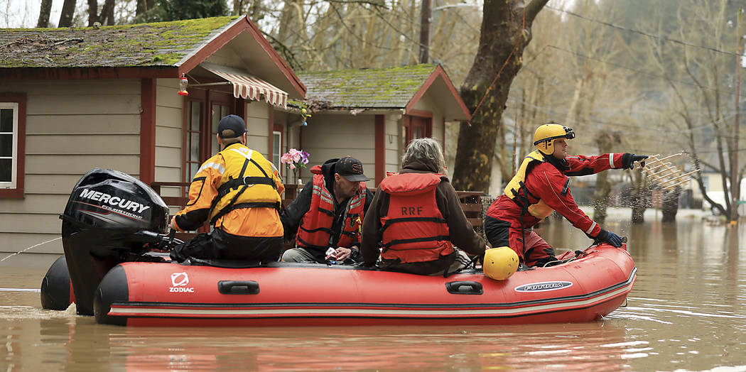 Ryan Lance, front, and Anthony Nash of the Russian River Fire Protection District swift-water rescue team rescue residents of Sycamore Court Apartment Wednesday, Feb. 27, 2019, in lower Guernevill ...