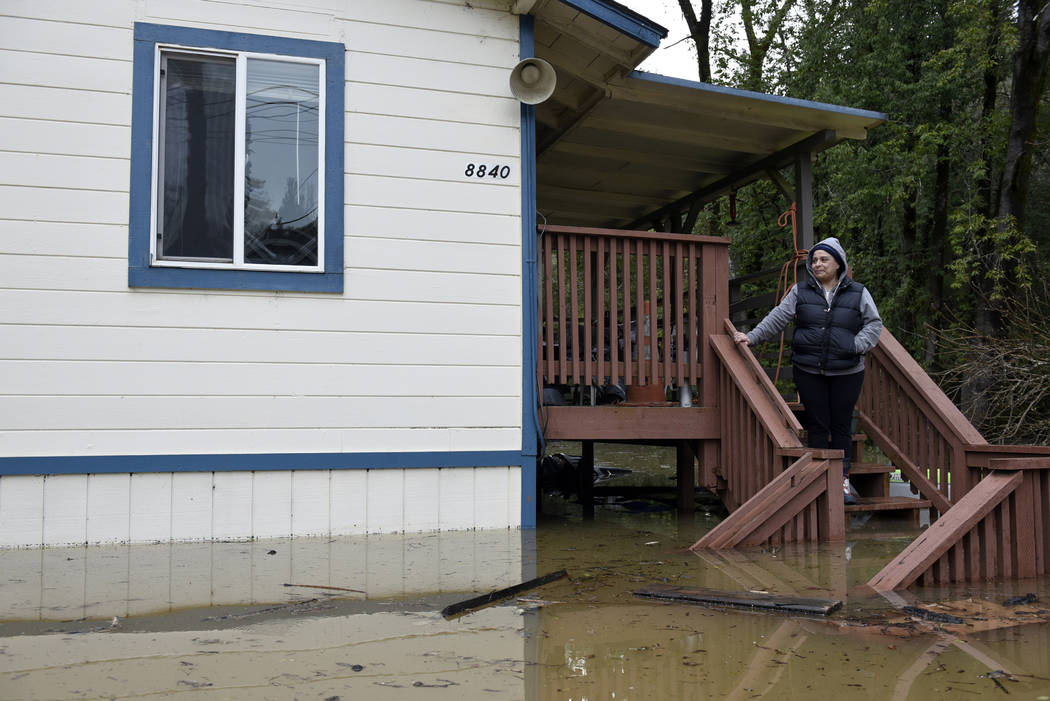 Amanda Hamner looks out at floodwaters from the Russian River surrounding her home in Forestville, Calif., on Wednesday, Feb. 27, 2019. The still-rising Russian River was engorged by days of rain ...