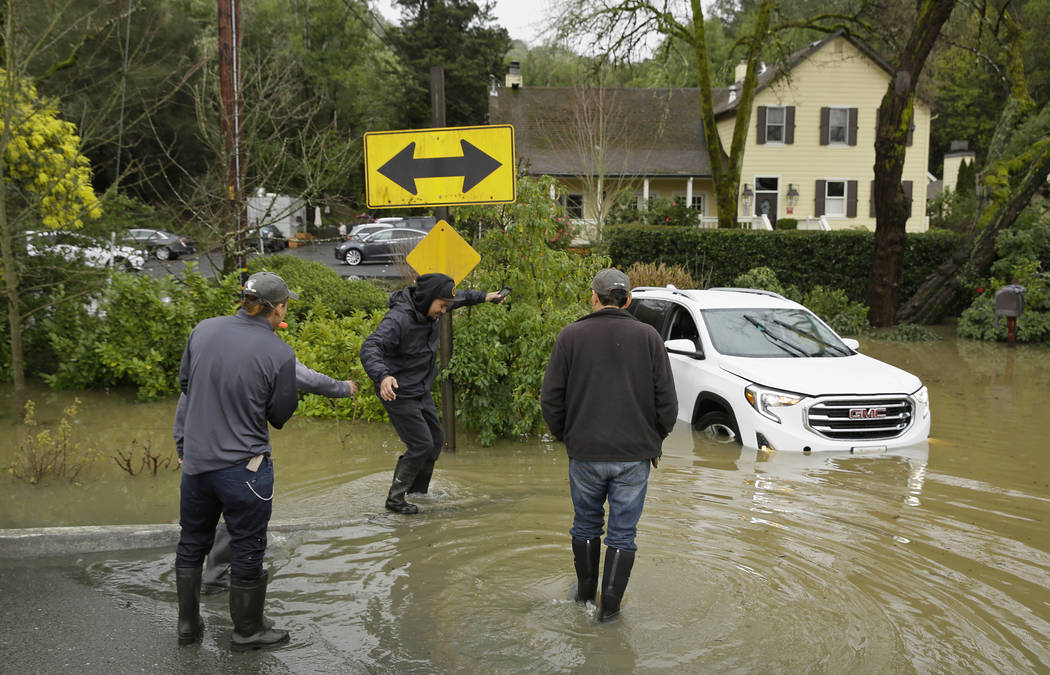 A group of men walk by a stranded car in flood water outside the Farmhouse Inn Wednesday, Feb. 27, 2019, in Forestville, Calif. (Eric Risberg/AP)