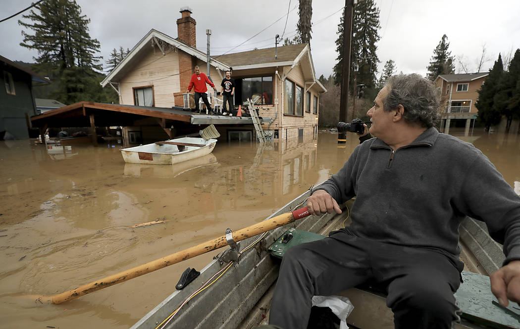 Jonathan Von Renner checks on his son Jonathan Jr., and friend Emilio Ontivares in lower Guerneville, Calif., Wednesday, Feb. 27, 2019. Two Northern California communities are accessible only by b ...